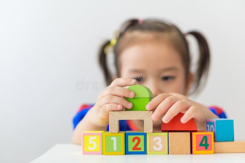 Азиатская девушка играя деревянные строительные блоки стоковые фото