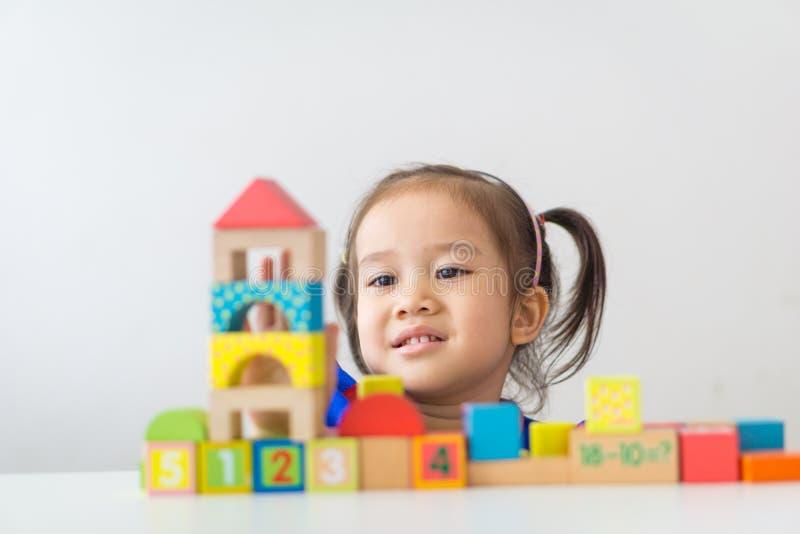 Азиатская девушка играя деревянные строительные блоки стоковое фото rf