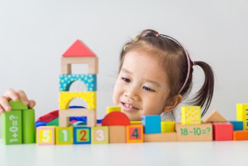 Азиатская девушка играя деревянные строительные блоки стоковое изображение