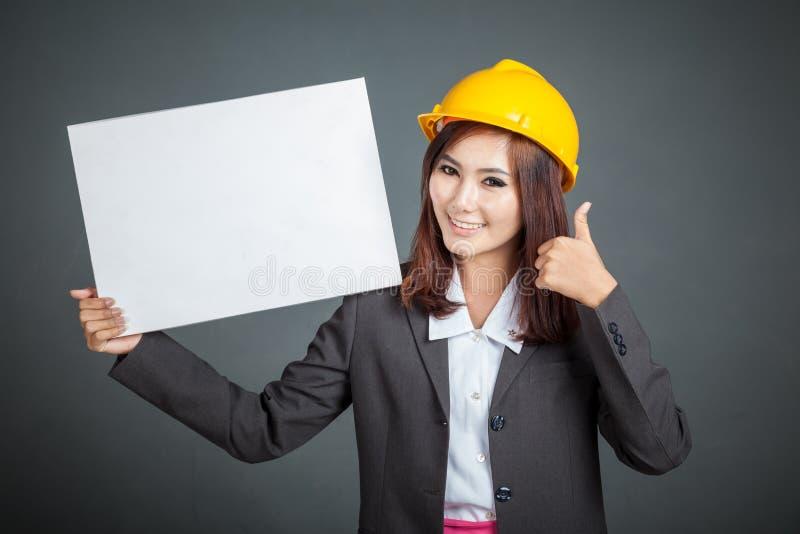 Азиатская девушка инженера thumbs вверх с пустым знаком стоковая фотография