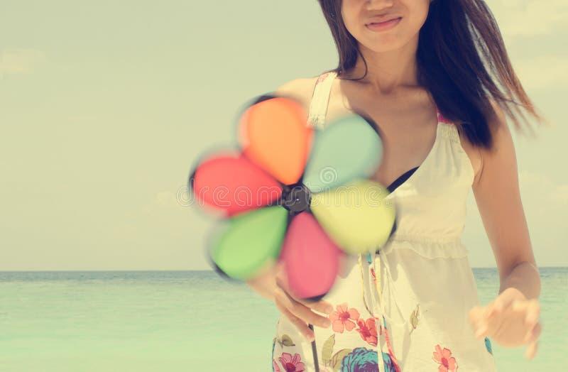 Азиатская девушка используя pinwheel на пляже стоковое изображение