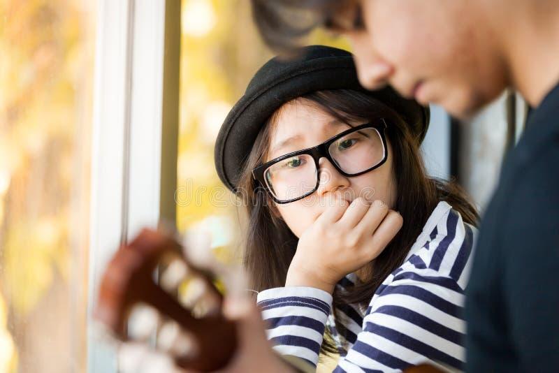 Азиатская девушка смотря ее парня играя гитару с влюбленностью стоковая фотография