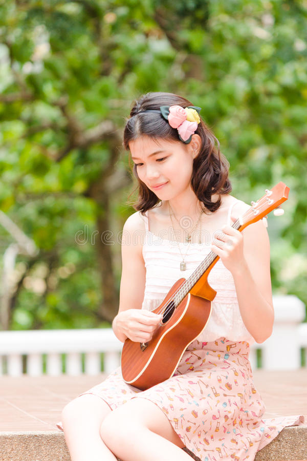 Азиатская девушка с гитарой гавайской гитары внешней стоковая фотография