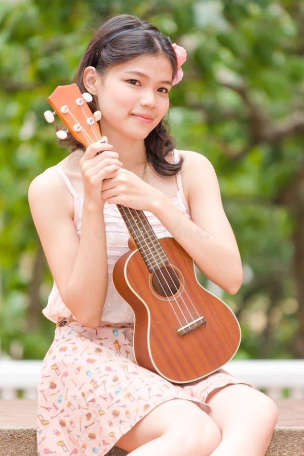 Азиатская девушка с гитарой гавайской гитары напольной стоковая фотография