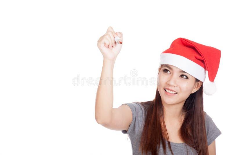 Азиатская девушка с красной шляпой santa пишет в воздухе и улыбке стоковые изображения rf