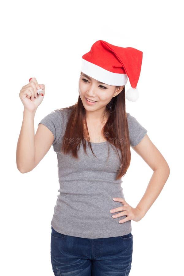 Азиатская девушка с красной шляпой santa пишет в воздухе и улыбке стоковая фотография