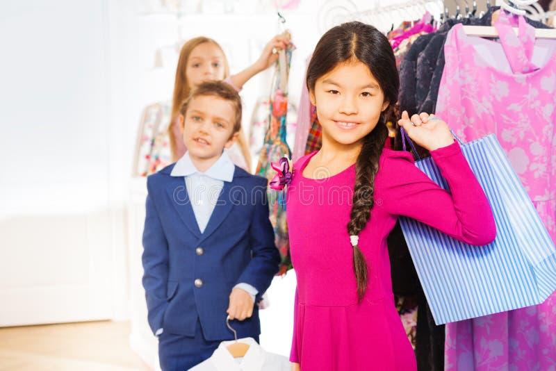 Азиатская девушка с хозяйственной сумкой и друзьями в магазине стоковое фото