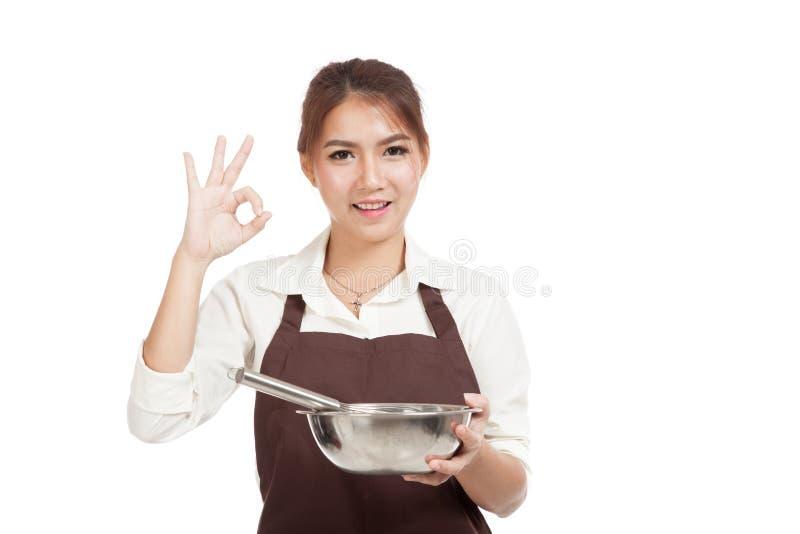 Азиатская девушка хлебопека с знак О'КЕЙ выставки юркнет и шара стоковое фото