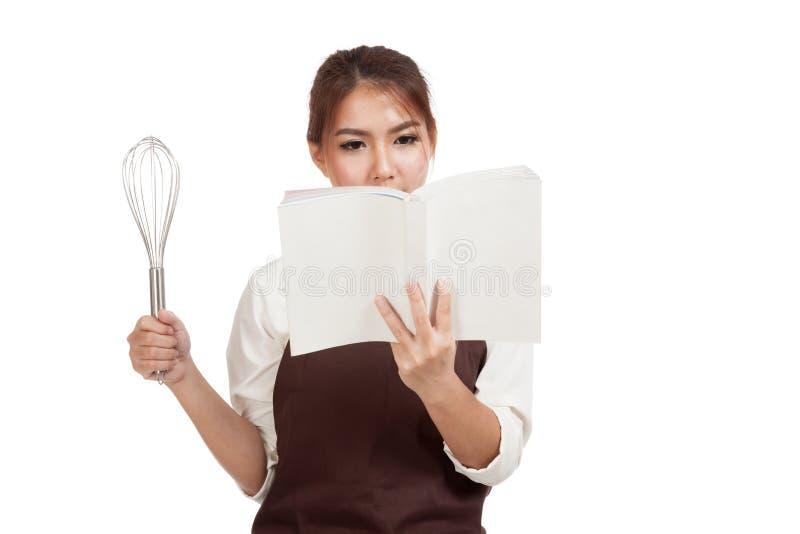 Азиатская девушка хлебопека с юркнет и варит книга стоковая фотография