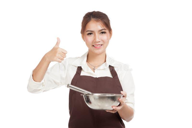 Азиатская девушка хлебопека с юркнет и выставка шара thumbs вверх стоковые изображения
