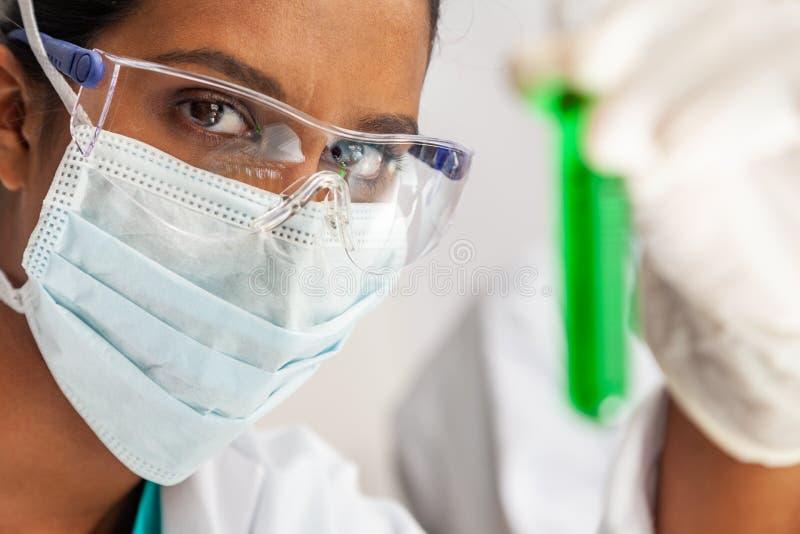 Азиатская женская исследовательская лабаратория медицинского исследования ученого с пробиркой зеленого решения стоковое фото