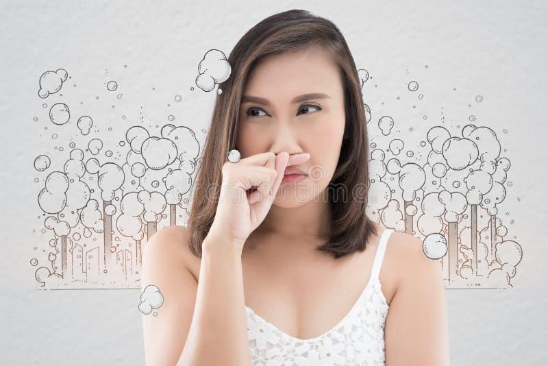 Азиатская женщина в белом платье улавливает ее нос из-за плохого запаха стоковое изображение rf