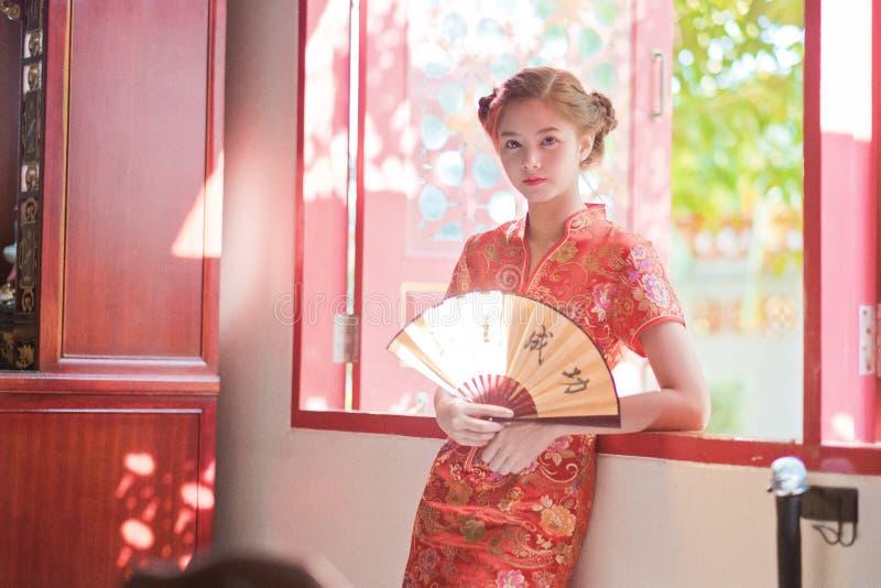 Азиатская женщина в китайце одевает держать двустишие 'успех' (Chin стоковое изображение rf