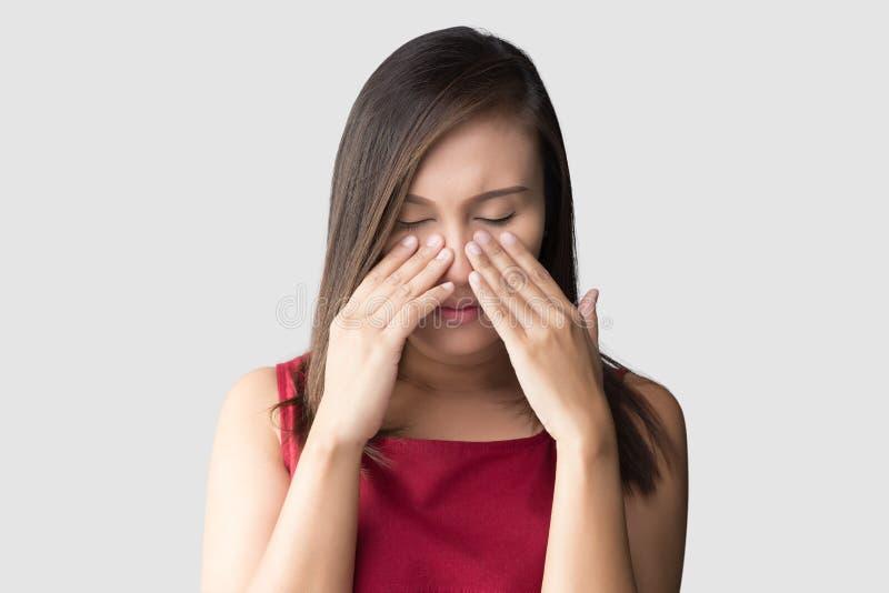 Азиатская женщина в красном чувстве носки нездоровом из-за синуса против серой предпосылки Люди уловили холод и лихорадку стоковое фото rf