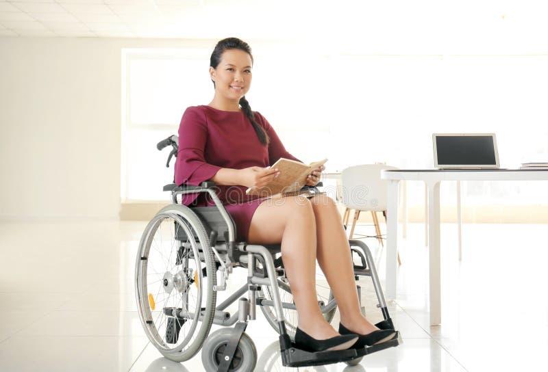 Азиатская женщина в кресло-коляске с тетрадями на работе стоковое фото rf