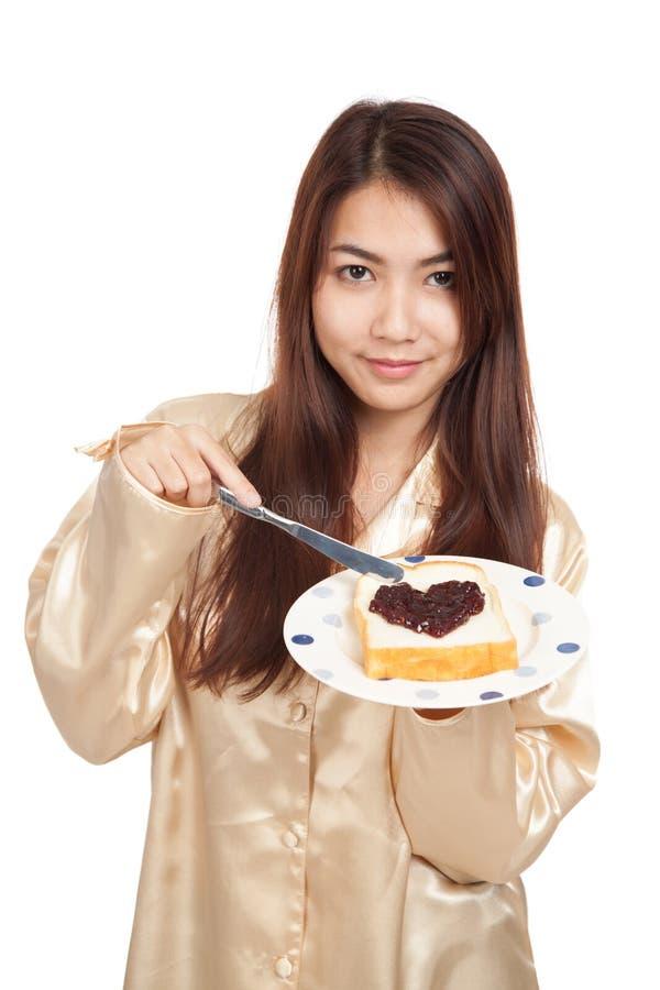 Азиатская женщина в пижамах с ягодой формы хлеба и сердца сжимает стоковые изображения