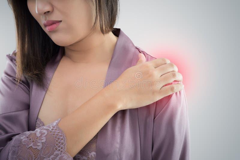 Азиатская женщина в фиолетовом nightwear сатинировки отжимая ее руку против стоковая фотография rf