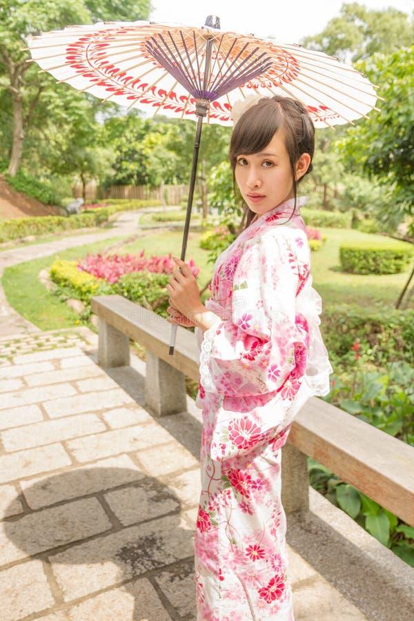 Азиатская женщина в yukata, держа зонтик в саде стоковое изображение
