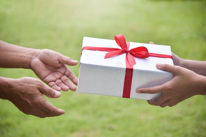 Азиатская женщина давая белую подарочную коробку к пожилому человеку стоковые изображения