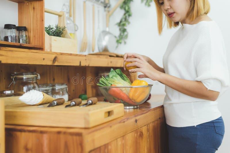 Азиатская женщина делая здоровую еду стоя счастливый усмехаться в кухне подготавливая салат Красивая жизнерадостная азиатская мол стоковое фото rf