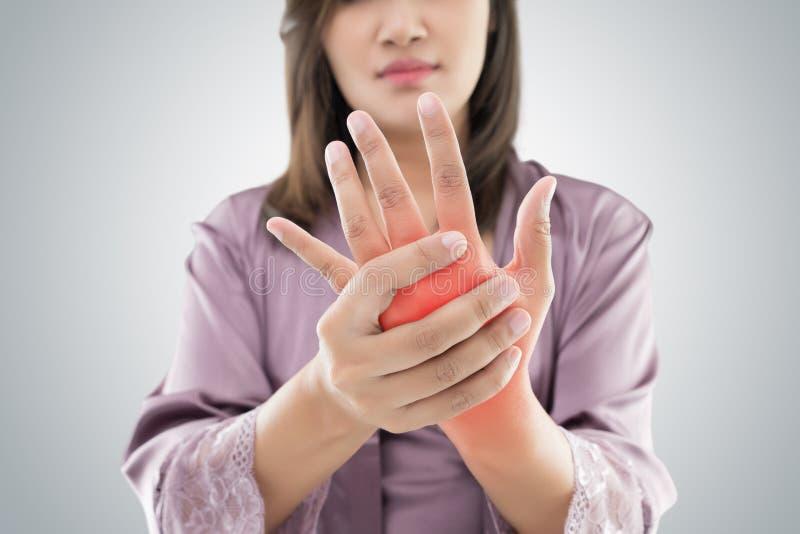Азиатская женщина держа ее руку против серой предпосылки, мучит conc стоковое фото rf