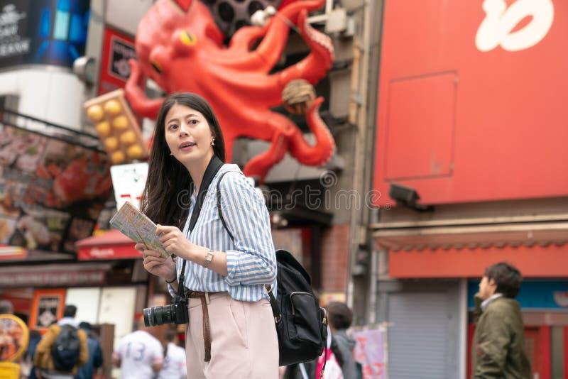 Азиатская женщина держа карту и ища место стоковое изображение