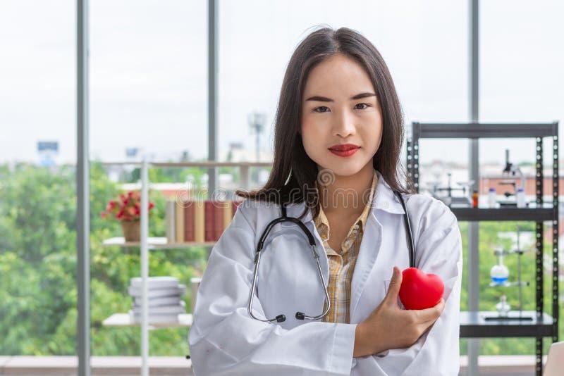 Азиатская женщина доктора диетолога показывая красное сердце в правой руке стоковые фото