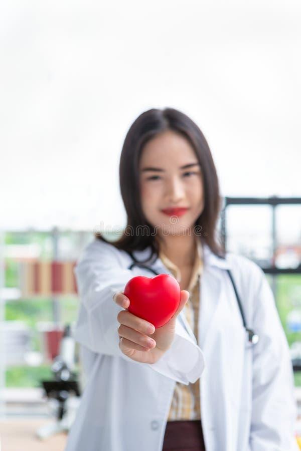 Азиатская женщина доктора диетолога показывая красное сердце в правой руке стоковое фото rf