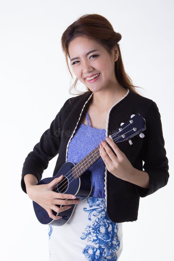 Азиатская женщина играя гавайскую гитару стоковые фото