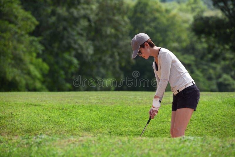 Азиатская женщина играя гольф на красивом естественном поле для гольфа стоковое изображение