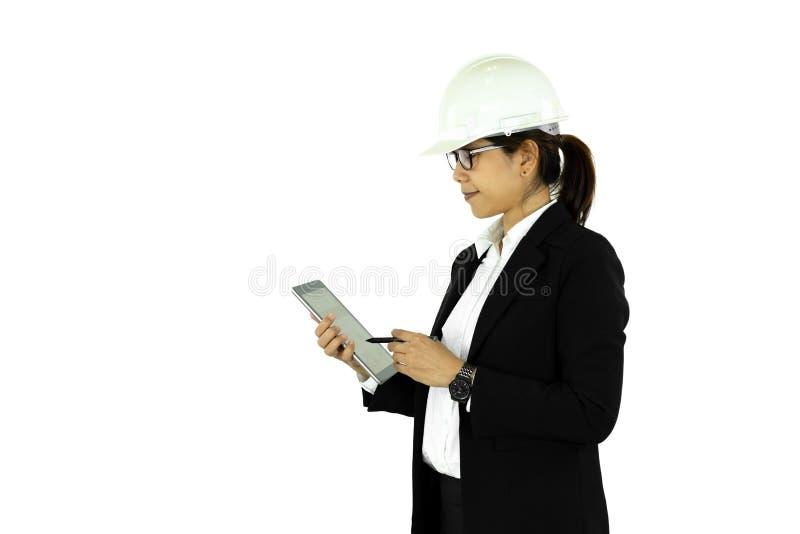 Азиатская женщина инженера в белом шлеме используя планшет, изолированный на w стоковое фото