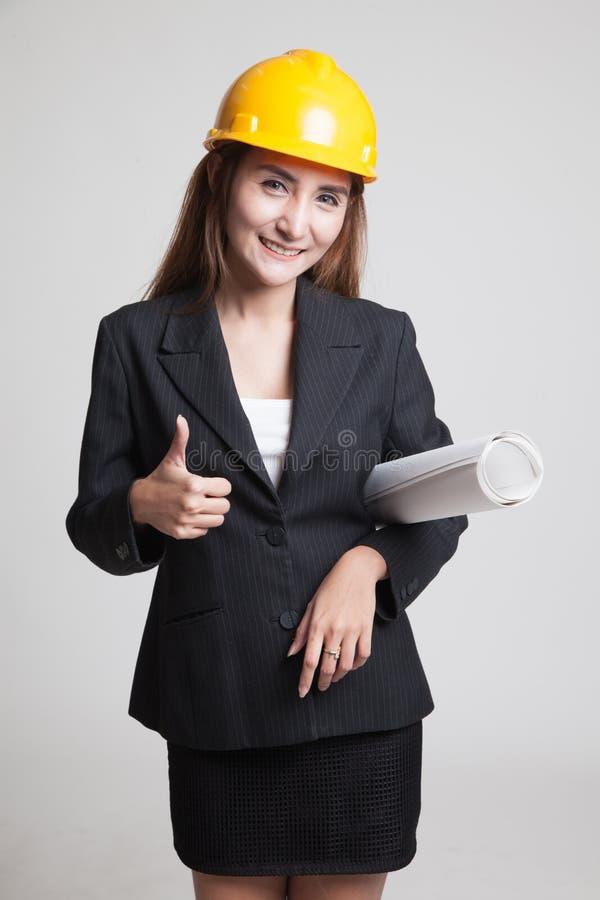 Азиатская женщина инженера с светокопиями показывает большие пальцы руки вверх стоковые изображения rf