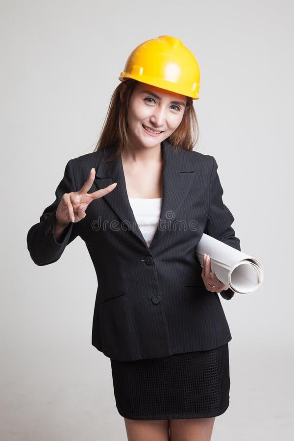 Азиатская женщина инженера с светокопиями показывает знак победы стоковые изображения rf