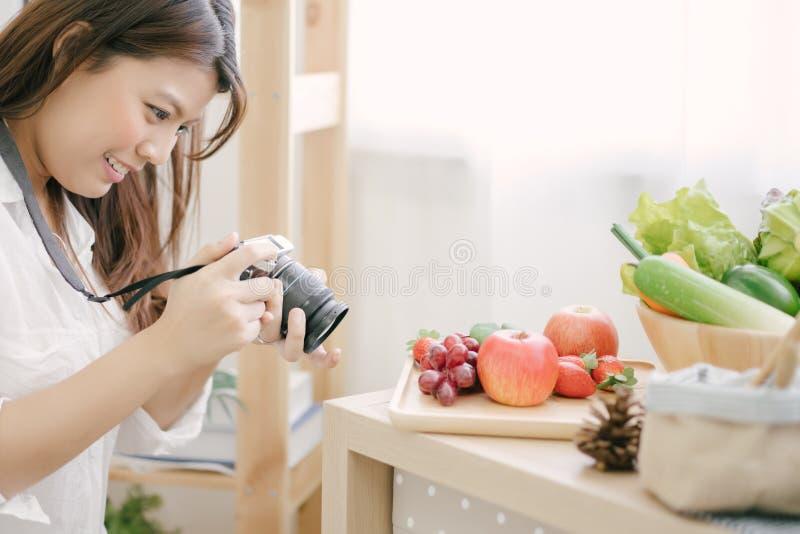 Азиатская женщина используя камеру фотографируя к овощам на кухне таблицы стоковые фотографии rf