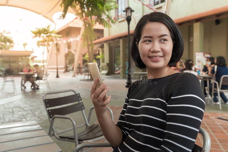 Азиатская женщина используя мобильный телефон стоковое изображение rf