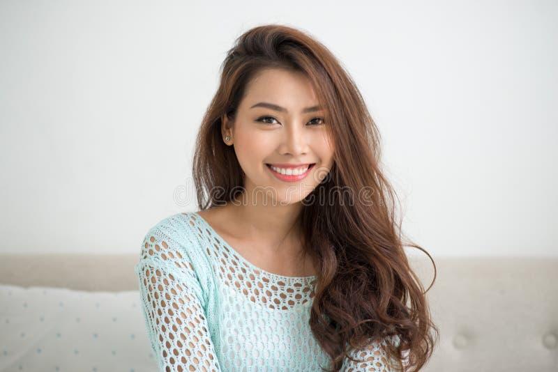Азиатская женщина используя smartphone сидя на кресле стоковая фотография