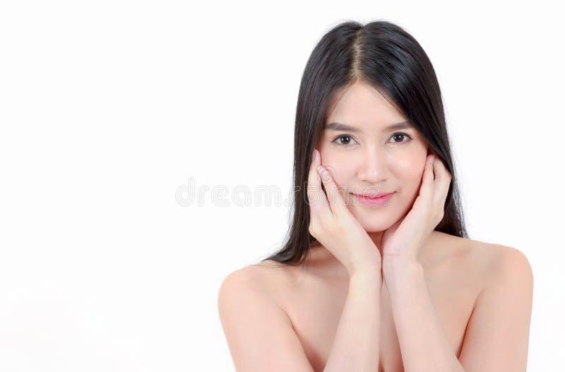 Азиатская женщина касаясь ее стороне и улыбке стоковая фотография