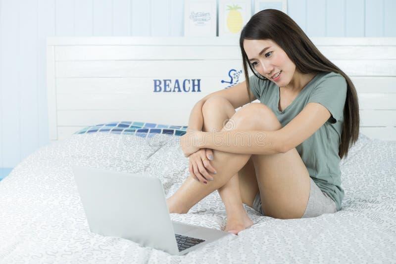 Азиатская женщина красоты сидя на кровати с компьтер-книжкой компьютера стоковые изображения