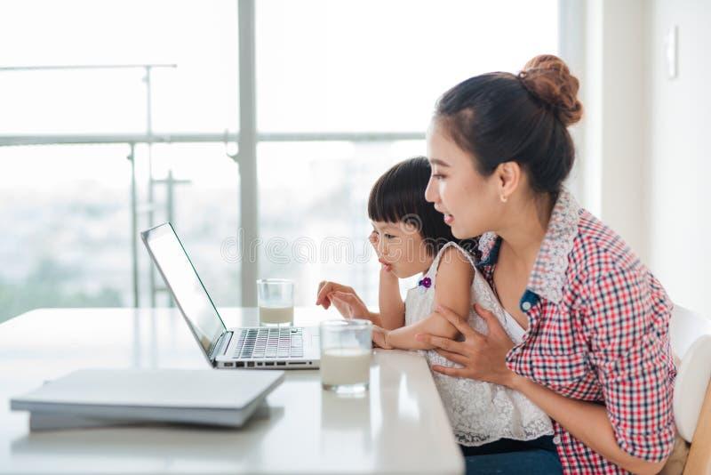 Азиатская женщина матери при ее дочь работая на компьютере стоковое изображение rf