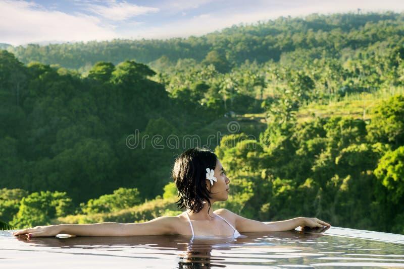 Азиатская женщина наслаждаясь горным видом в бассейне стоковая фотография rf