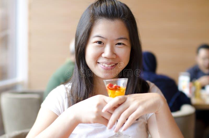 Азиатская женщина наслаждаясь ее десертом стоковая фотография rf