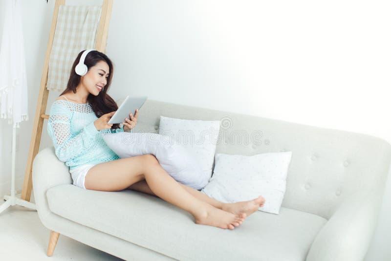 Азиатская женщина наслаждаясь сидеть на кресле и слушать к музыке стоковые изображения