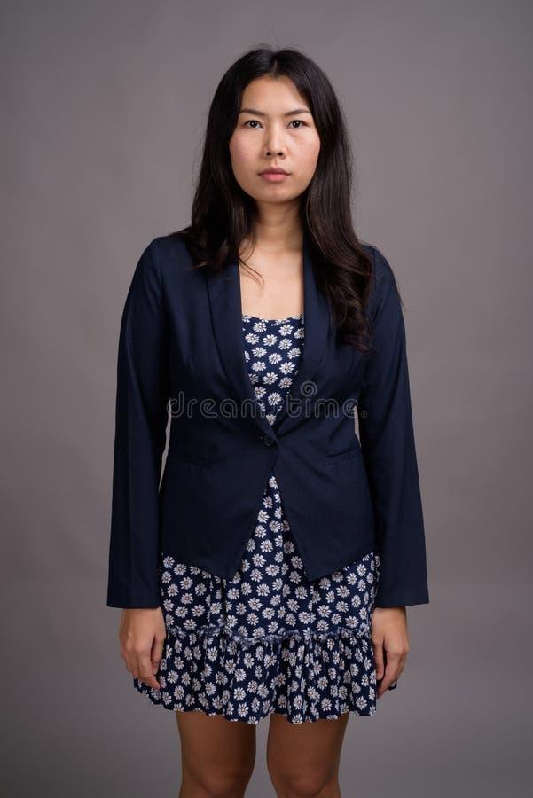 Азиатская женщина нося голубой свитер платья и кардигана против серого цвета стоковая фотография
