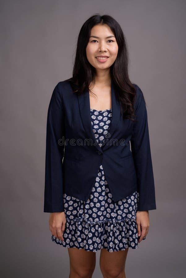 Азиатская женщина нося голубой свитер платья и кардигана против серого цвета стоковые фото