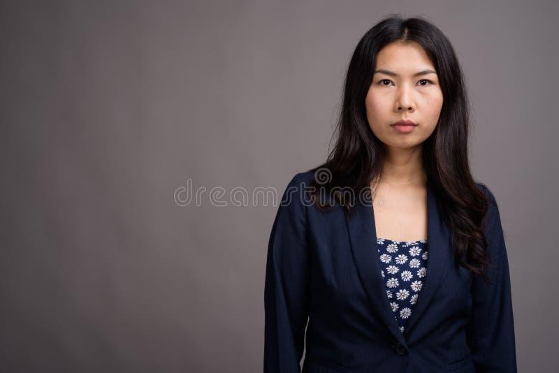 Азиатская женщина нося голубой свитер платья и кардигана против серого цвета стоковое фото rf