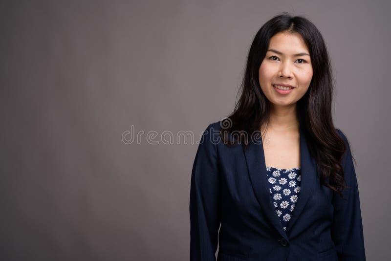 Азиатская женщина нося голубой свитер платья и кардигана против серого цвета стоковое изображение