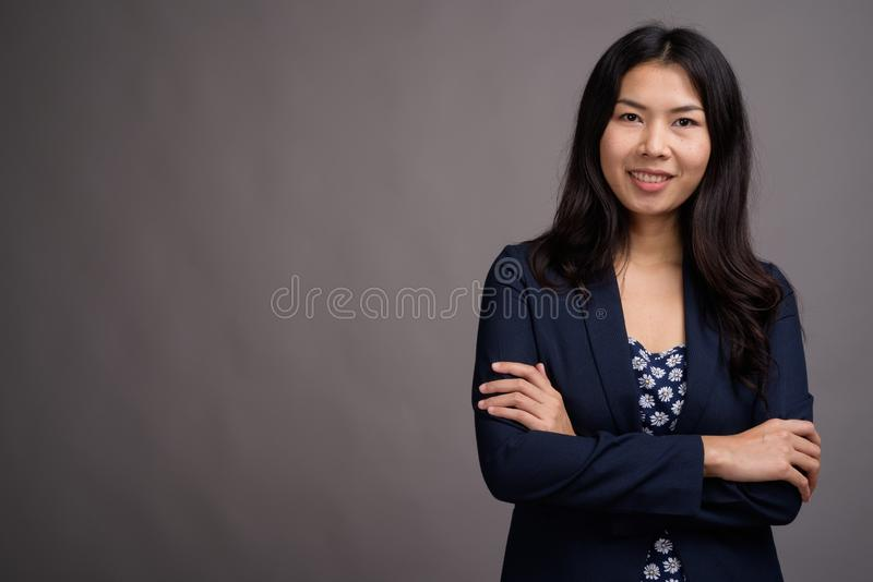 Азиатская женщина нося голубой свитер платья и кардигана против серого цвета стоковые фотографии rf