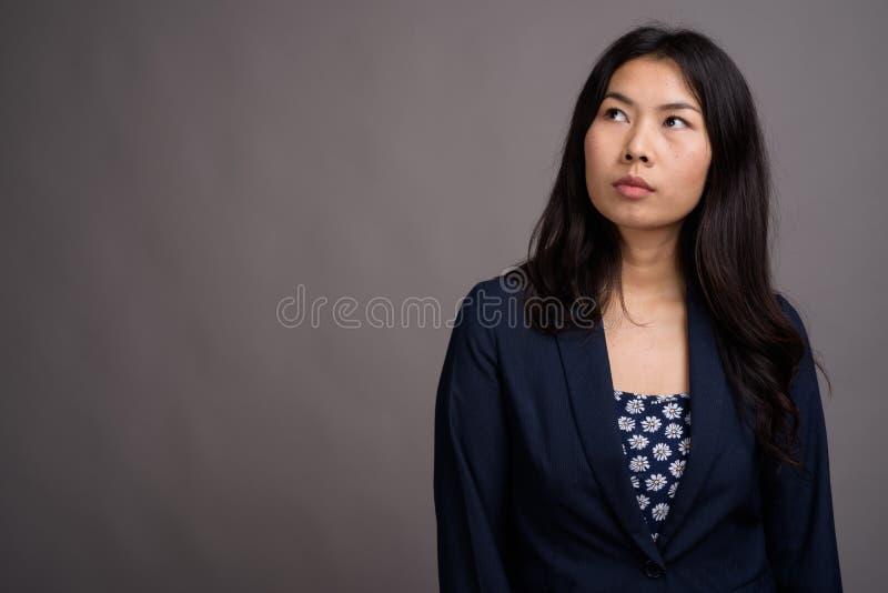 Азиатская женщина нося голубой свитер платья и кардигана против серого цвета стоковые изображения rf