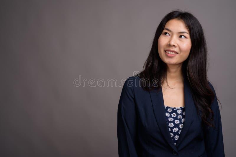 Азиатская женщина нося голубой свитер платья и кардигана против серого цвета стоковые изображения