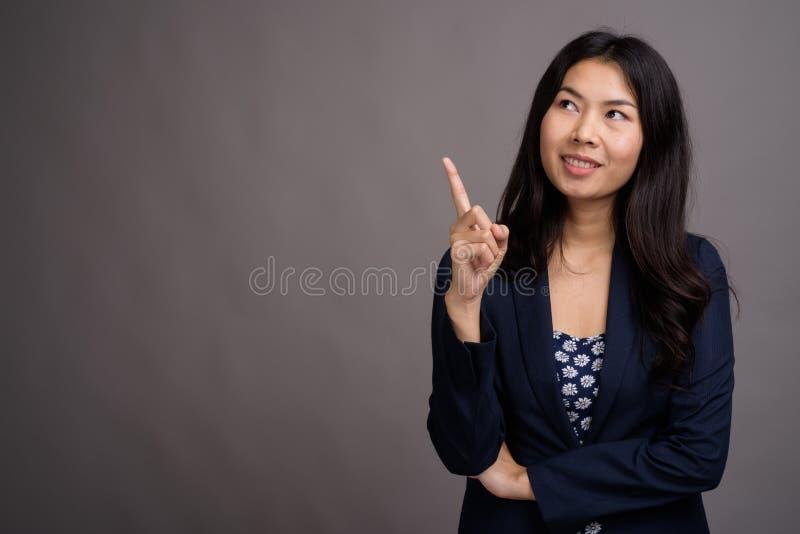 Азиатская женщина нося голубой свитер платья и кардигана против серого цвета стоковое изображение rf